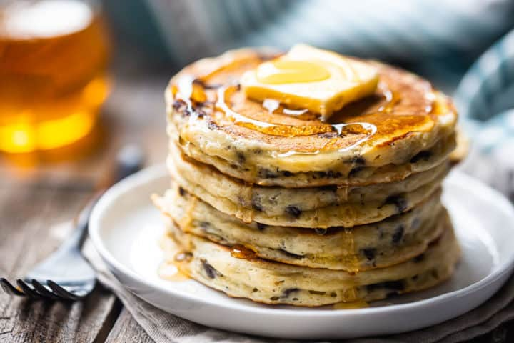 Homemade pancakes with chocolate chips, stacked on a plate and topped with butter and syrup.