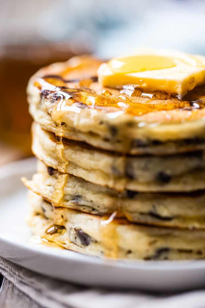 Close up image of the side of a stack of sky-high, fluffy chocolate chip pancakes.