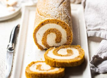 Pumpkin roll served on a rectangular white ceramic plate.