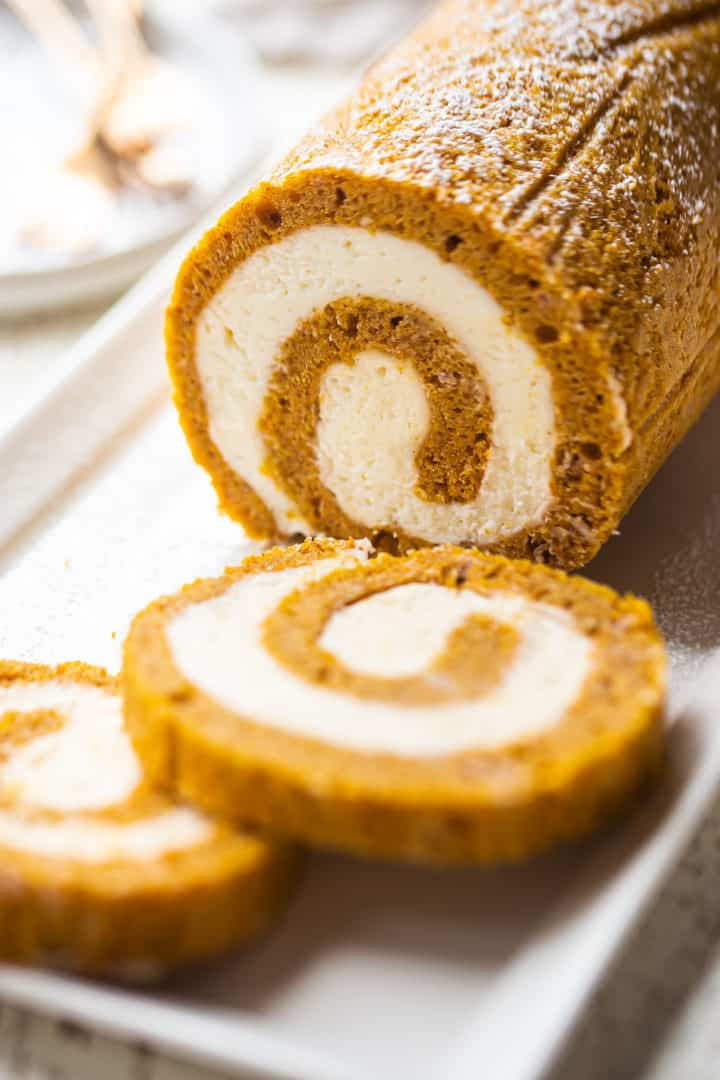 Close-up image of a pumpkin roll cake, showing the pumpkin spice sponge cake spiraled around the creamy filling.