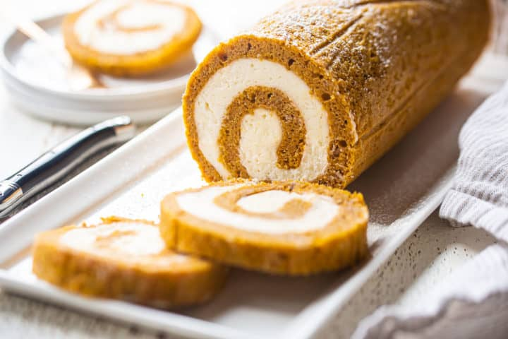 Easy pumpkin roll recipe, prepared and served on a white dish with a black-handled knife in the background.