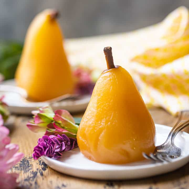 Poached pears served on small ceramic plates with pink flowers.