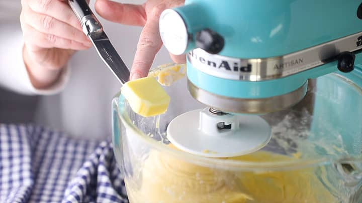 Working soft butter into brioche dough, a tablespoon at a time.
