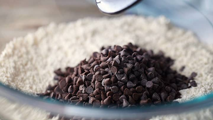 Adding mini chocolate chips to dry ingredients.