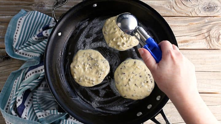 Making chocolate chip pancakes in a greased skillet.