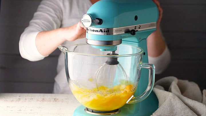Whipping eggs and sugar together on high speed.
