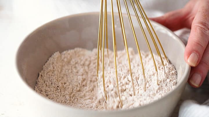Whisking dry ingredients together in a gray ceramic bowl.