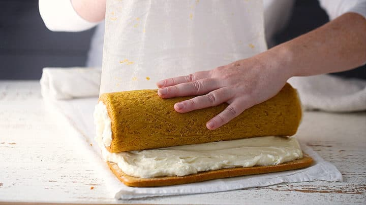 Rolling pumpkin cake into a cylinder with cream cheese filling.