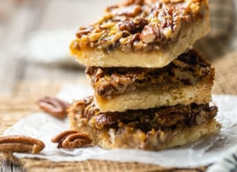 Pecan pie bars stacked on waxed paper, with whole pecans in the background.