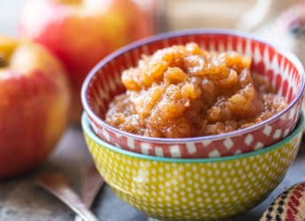 Applesauce in a colorful bowl, with apples in the background.