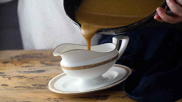 Pouring gravy from pan into serving dish.