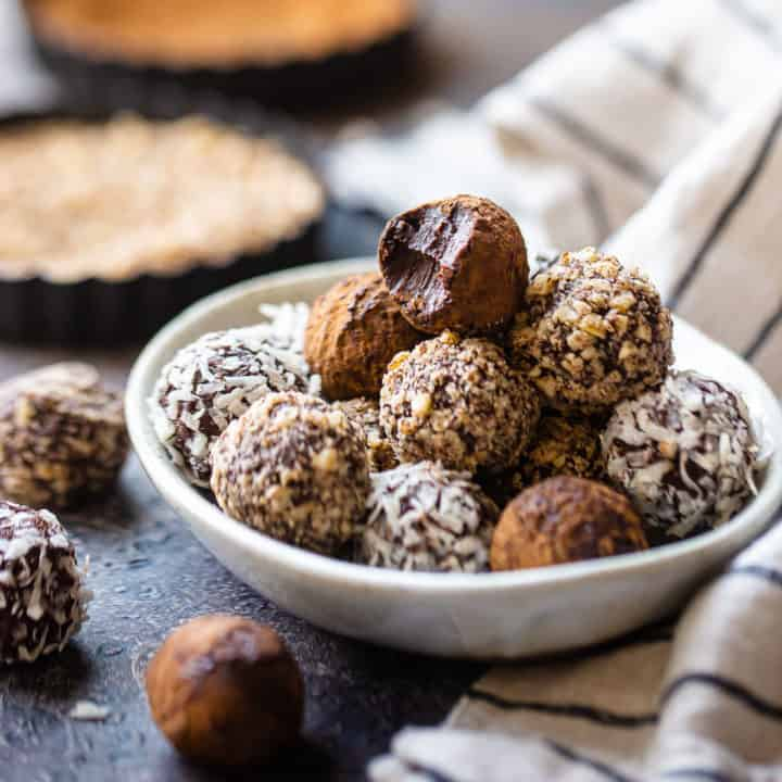 Chocolate truffles stacked in a pottery dish with tins of crushed nuts in the background.