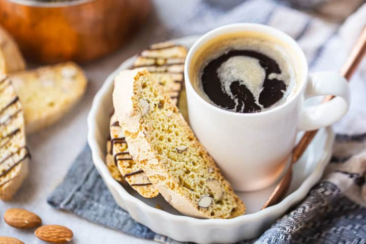 Almond biscotti recipe, prepared and served in a white ceramic dish with a cup of coffee.