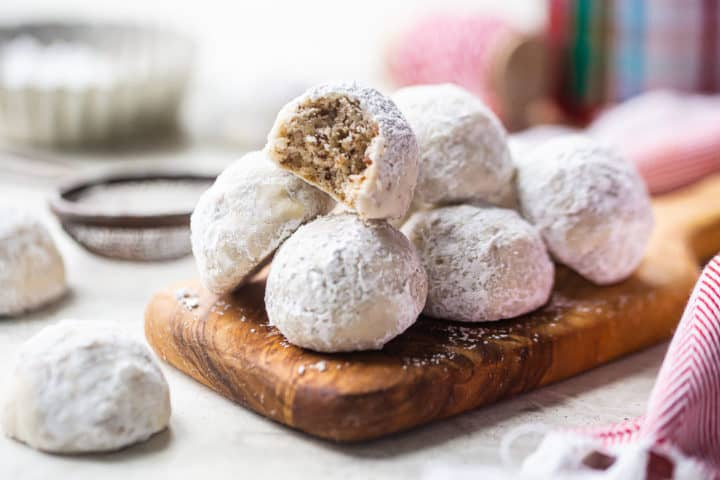 Snowball cookie recipe, prepared and served on a wooden tray with powdered sugar in the background.