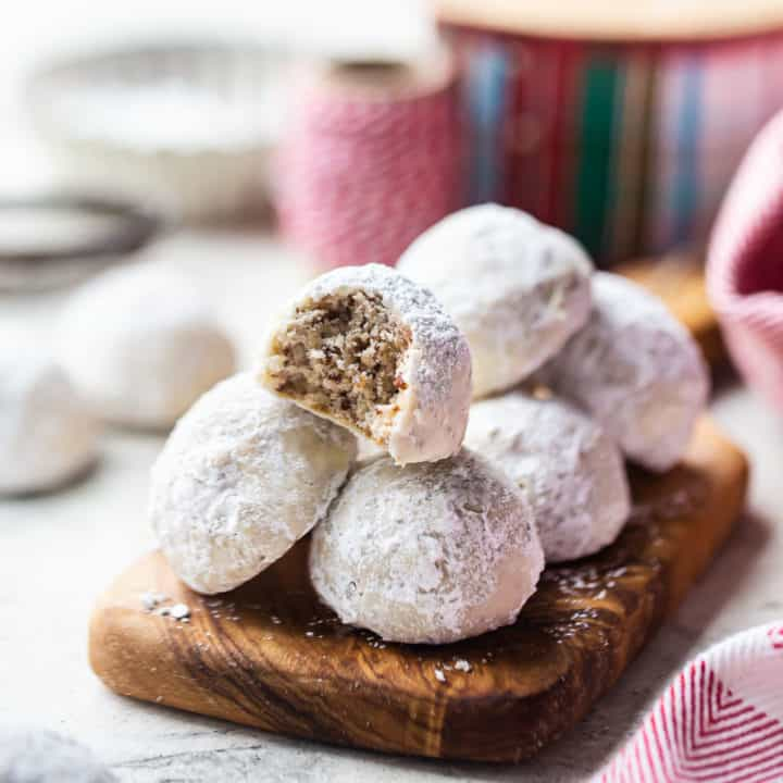 Mexican wedding cookies piled on a wooden board with Christmas ribbon in the background.