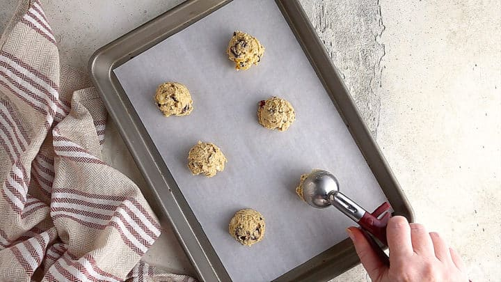 Scooping oatmeal cranberry cookie dough onto a baking sheet.