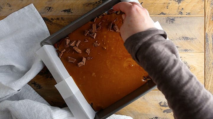 Sprinkling chocolate over hot toffee.