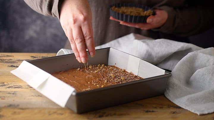 Garnishing homemade toffee with crushed nuts.