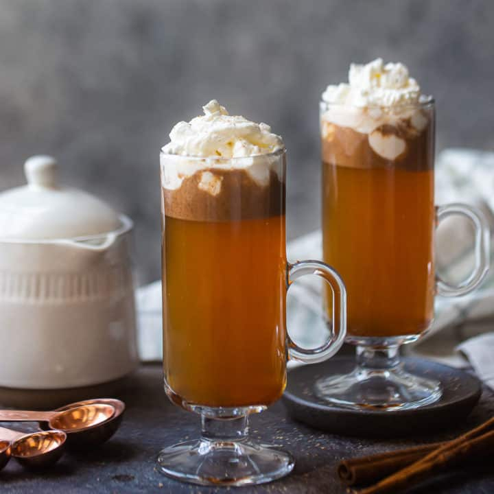 Two tall mugs of hot buttered rum, with a teakettle in the background.