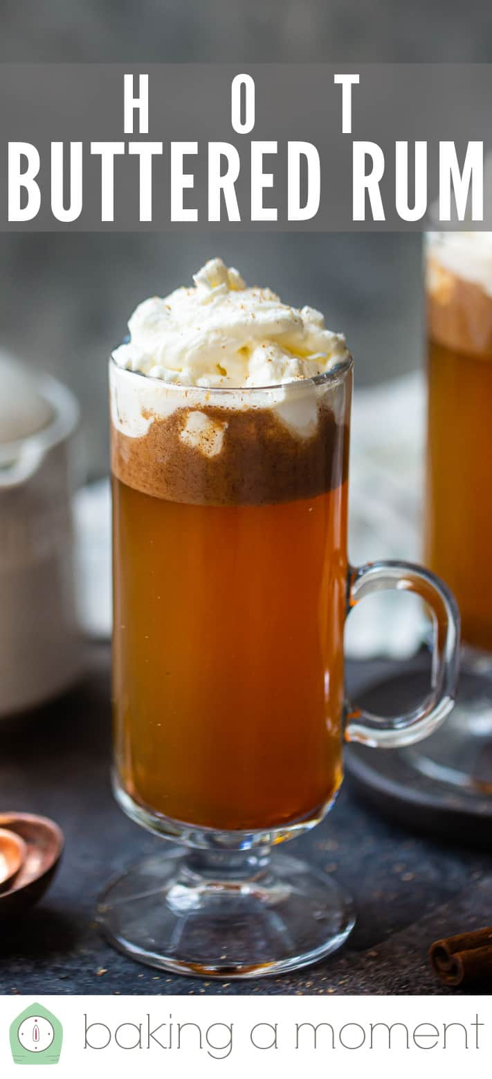 Tall glass mug of hot buttered rum with a text overlay above.