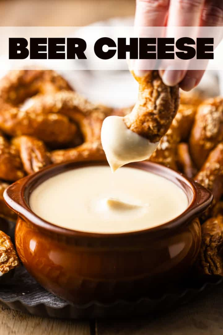 """Dipping a pretzel into a bowl of beer cheese dip, with a text overlay above that reads """"Beer Cheese."""""""