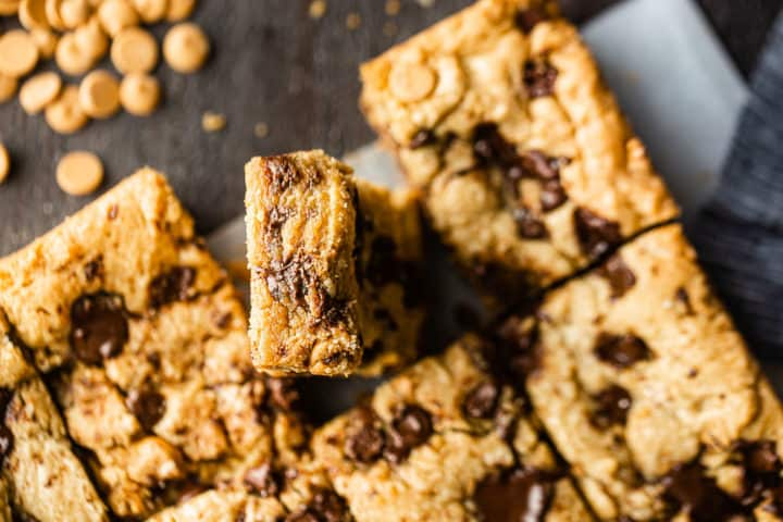 Overhead image of a peanut blondie recipe, cut into squares with one bar tilted up to show the gooey inside.