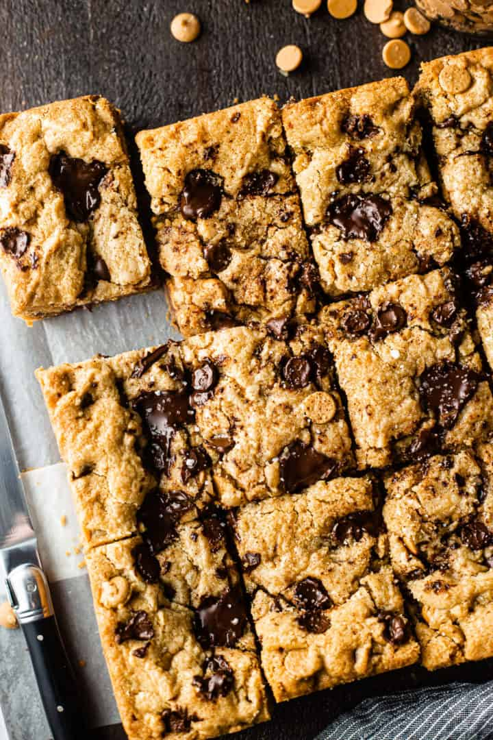 Overhead image of peanut butter chocolate chip blondies on a sheet of parchment paper with a knife.