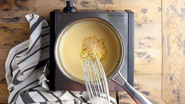 Whisking dry mustard and garlic powder into beer cheese.