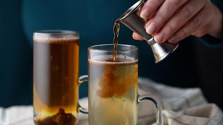 Adding rum to the serving mug.