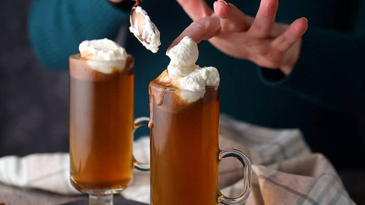 Topping the drinks with whipped cream.