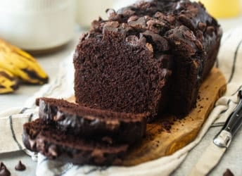 Chocolate banana bread presented on a wooden board with bananas in the background.
