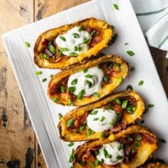 Potato skins served on a white rectangular platter.