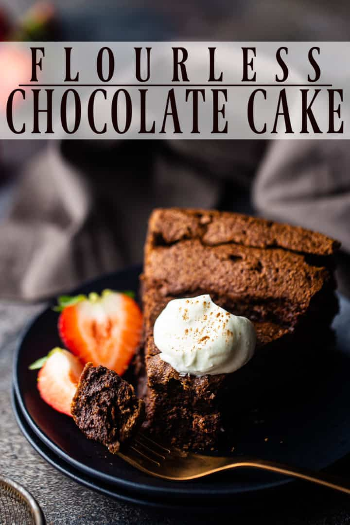 Flourless chocolate cake recipe, baked and served on a dark plate with fresh strawberries.