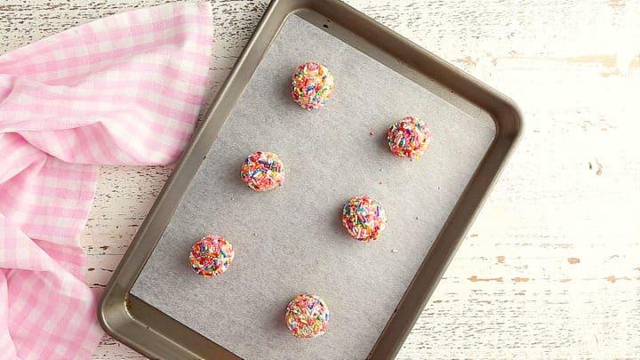 Unbaked funfetti cookies on a baking sheet.