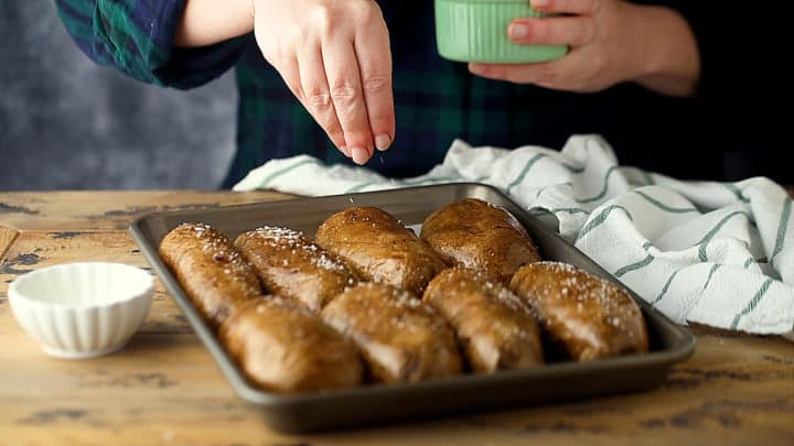 Sprinkling oiled potato skins with salt.