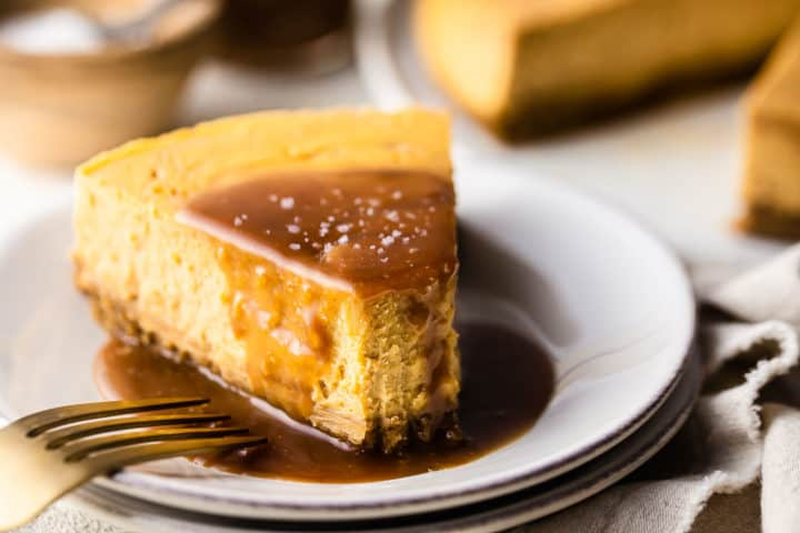 Salted caramel cheesecake recipe, baked, sliced and served on a white plate with a gold fork.