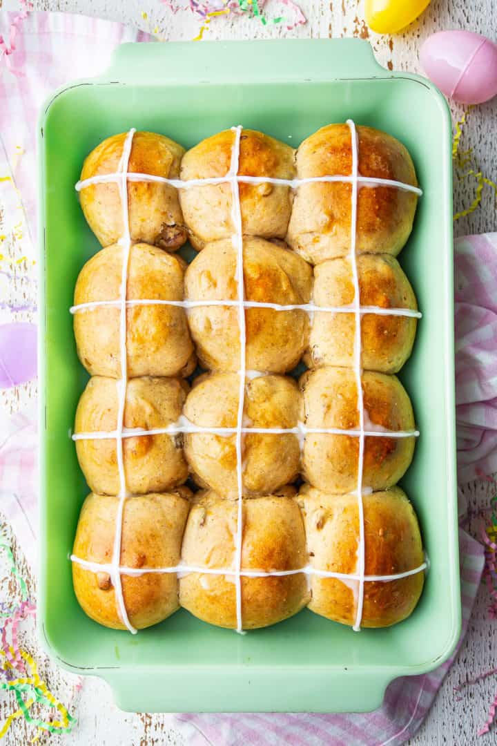 Overhead image of what are hot cross buns with a cross piped over the top in sweet confectioners icing.