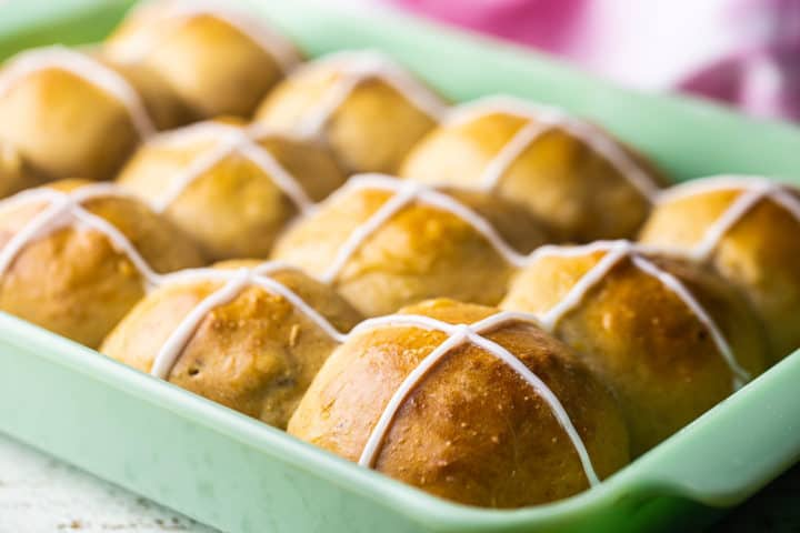 Close up image of cross buns with dried fruit, spices, and a sweet icing on top.