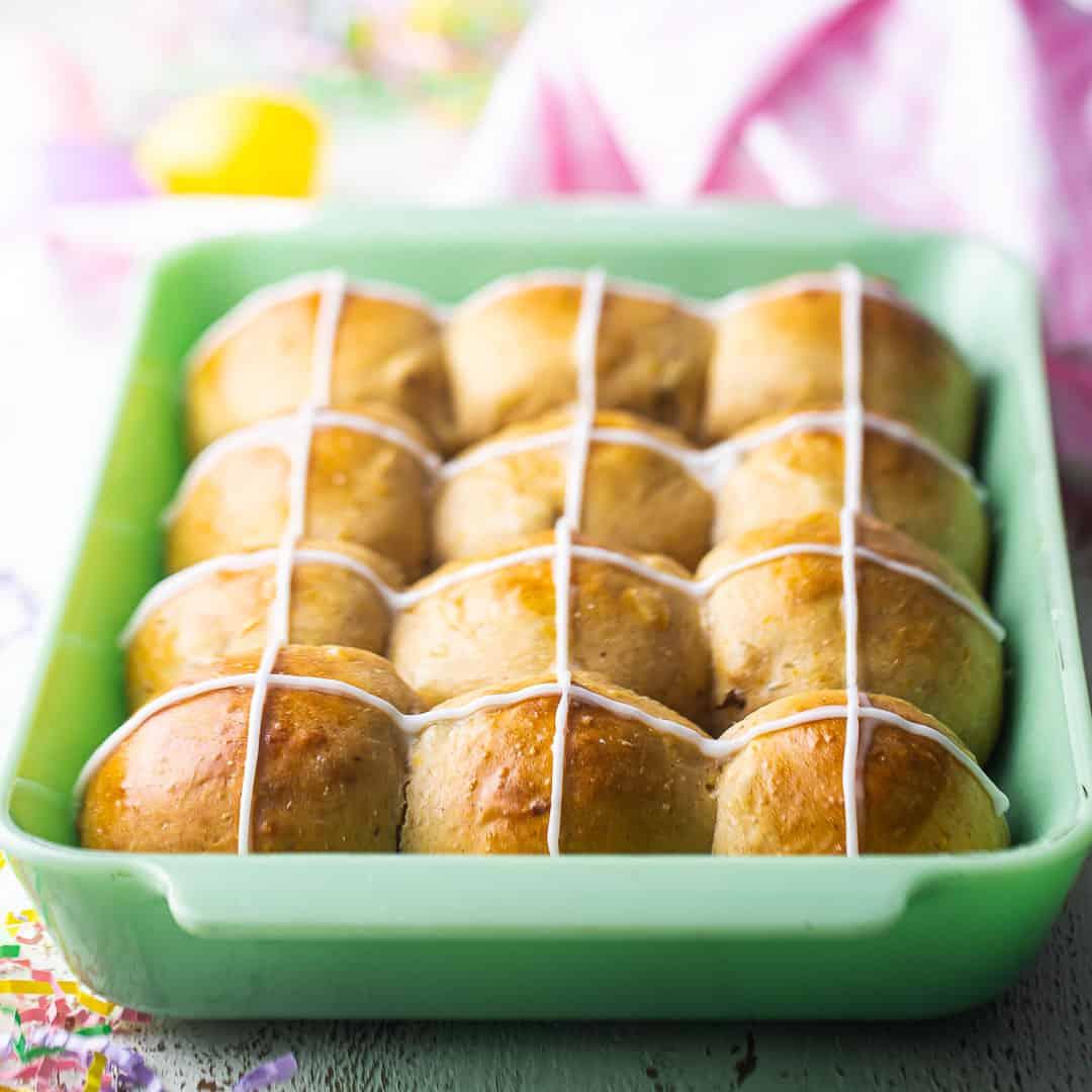Hot cross buns baked in a rectangular jadeite baking dish.