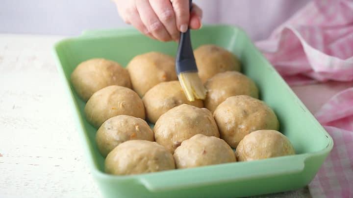 Brushing hot cross buns with egg white before baking.
