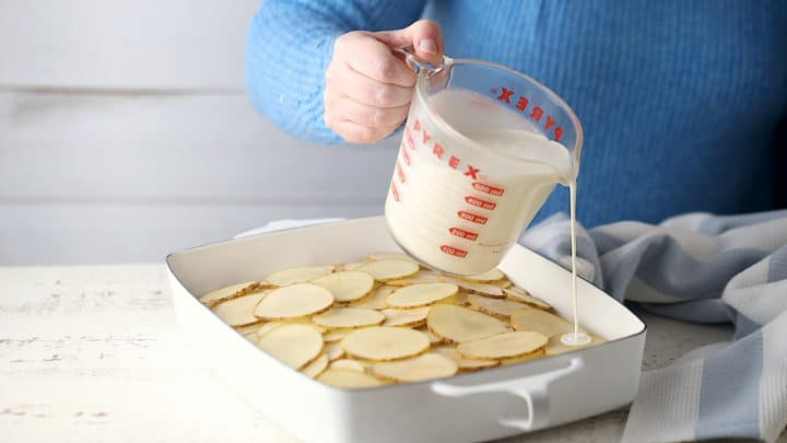 Submerging the sliced potatoes in the cream/milk mixture.