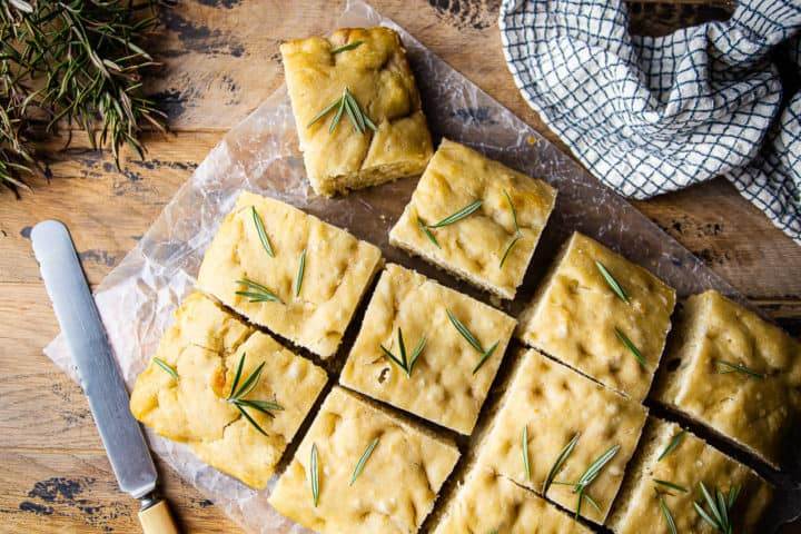 Overhead image of focaccia bread recipe, prepared and garnished with sea salt and fresh herbs.