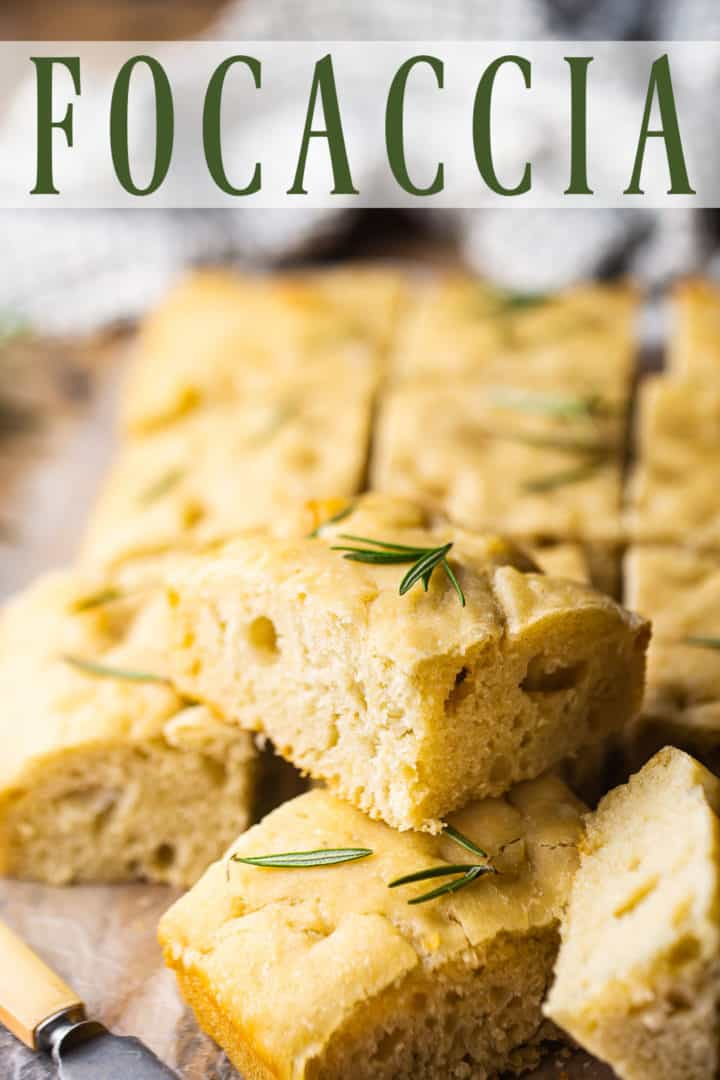 Focaccia bread cut into squares and served on a wooden board with sea salt and rosemary.