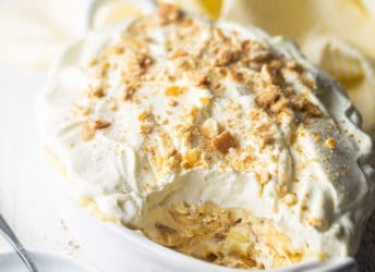 Banana pudding in an oval serving dish with crushed vanilla wafer cookies on top.