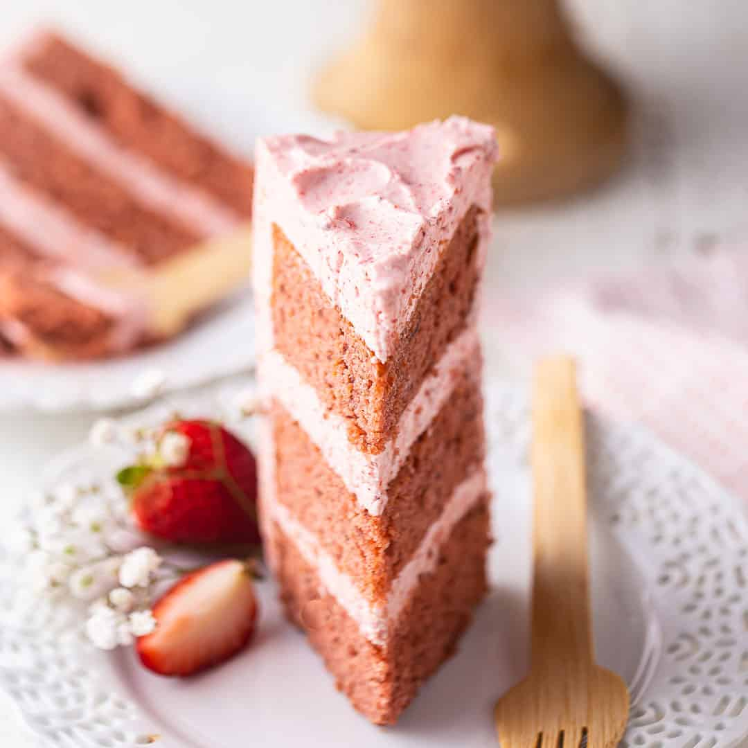 A slice of strawberry cake on a lacy white plate with a wooden fork.
