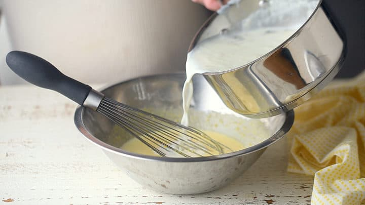 Tempering eggs with hot milk.