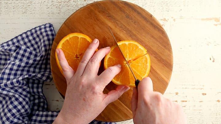 Cutting orange slices into quarters.