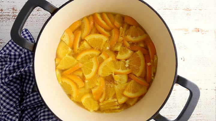 Simmering oranges in water to soften their peels.