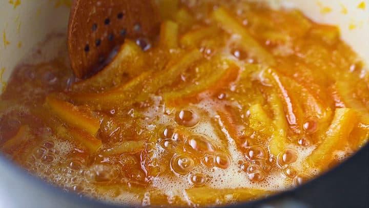 Boiling orange marmalade until gelled.